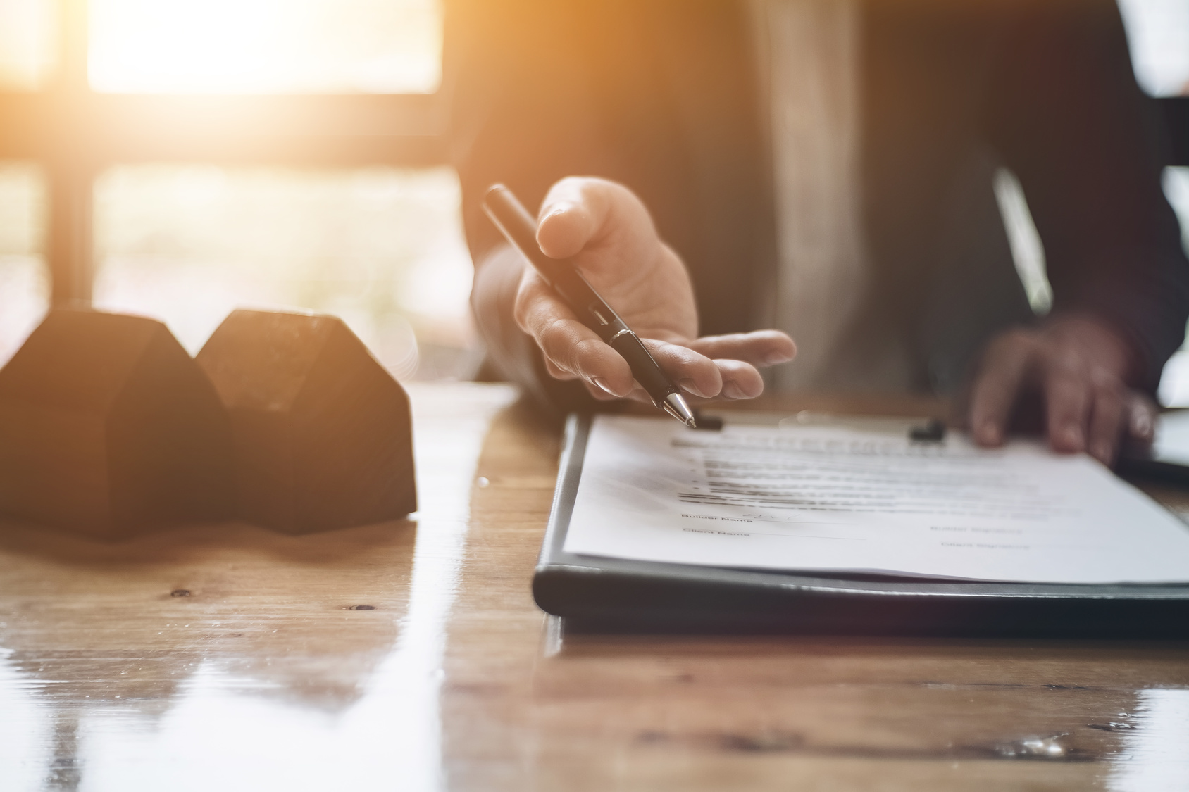 Man-Giving-Pen-to-Sign-Real-Estate-Documents