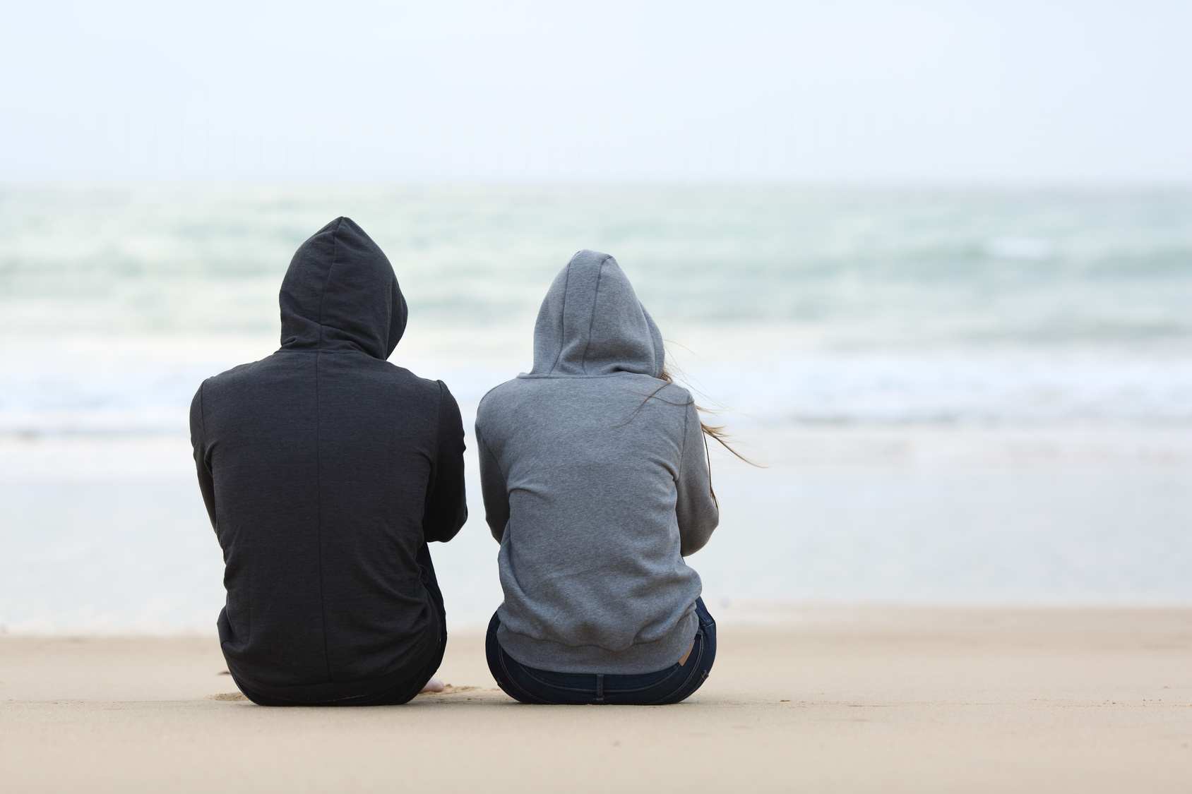 Two-People-Sitting-on-a-Beach